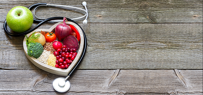 Health & Disease cover photo: healthy food in a heart shape surrounded by a stethoscope