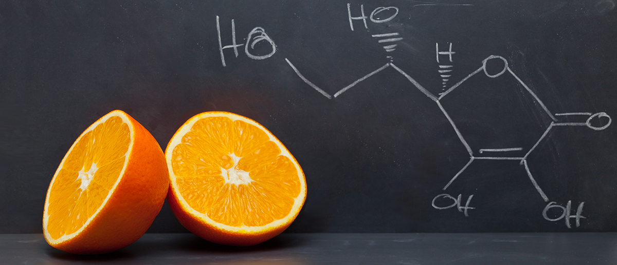 picture of an sliced orange and the chemical structure of vitamin C drawn on a chalkboard